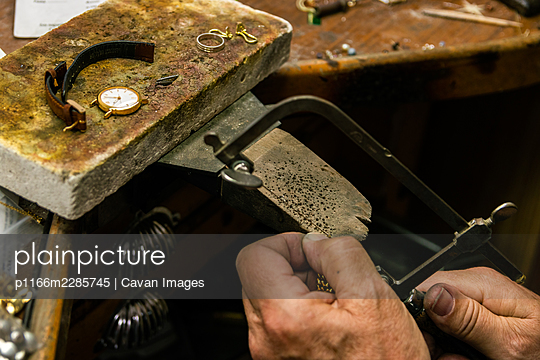 Men's hands in a jewelry workshop cutting piece of gold with hacksaw - p1166m2285745 by Cavan Images
