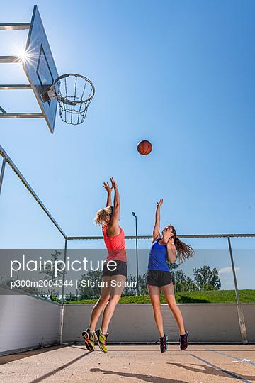 Young women playing basketball - p300m2004344 von Stefan Schurr