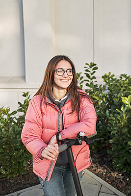 millennial young girl in a pink jacket on an electric scooter - p1166m2177281 by Cavan Images