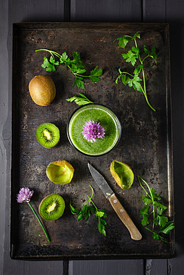 Glass of smoothie with kiwi, parsley and blooming chives, close up - p300m827137f by Elisabeth Cölfen