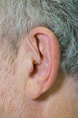 Cropped image of man wearing hearing aid - p301m1498504 by Halfdark