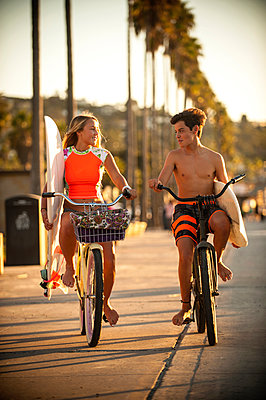 Teenage boy and girl riding bicycles carrying surfboards - p555m1231777 by Stephen Simpson Inc