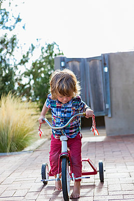 Caucasian boy riding tricycle in backyard - p555m1410484 by Marc Romanelli