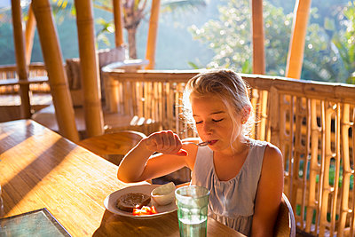 Caucasian girl eating on balcony - p555m1419321 by Marc Romanelli