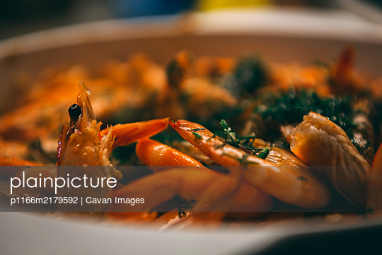 fried until golden brown tiger shrimp are ready in a pan and serving at the table - p1166m2179592 by Cavan Images