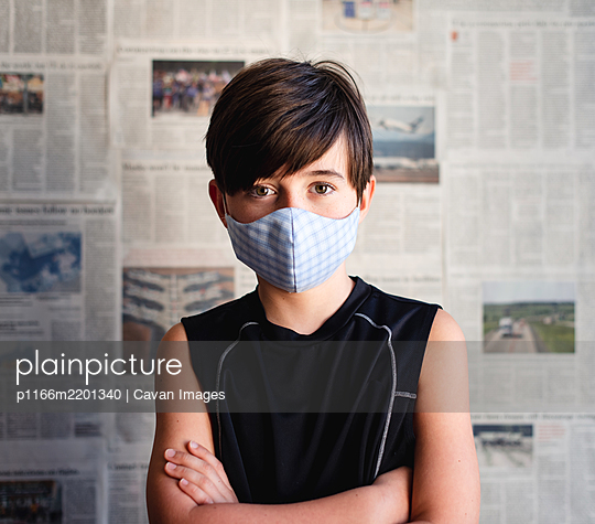 Boy wearing cloth mask against Covid 19 newspaper clippings. - p1166m2201340 by Cavan Images
