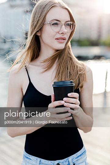 Young woman holding cup of coffee - p300m2041919 von Giorgio Fochesato