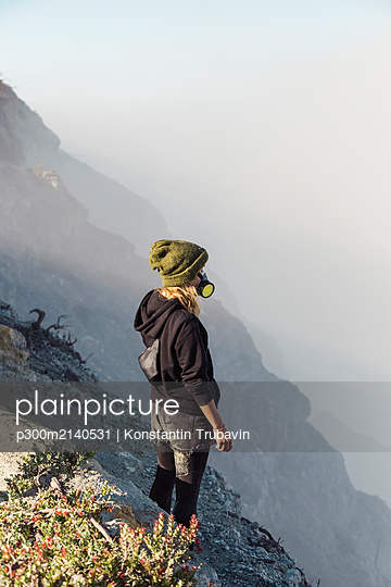 Young woman with respirator mask standing at the edge of volcano Ijen, Java, Indonesia - p300m2140531 by Konstantin Trubavin