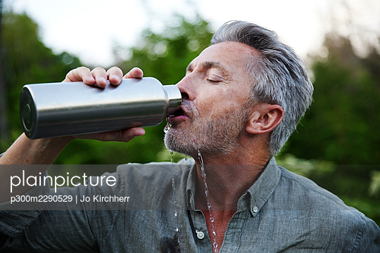 Thirsty man spilling while drinking water from bottle in forest - p300m2290529 by Jo Kirchherr