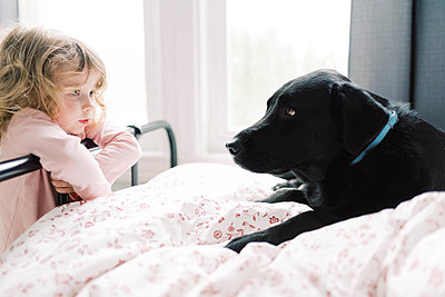 A little girl and her black Labrador. - p1166m2157456 by Cavan Images
