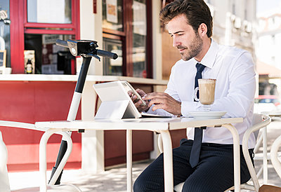 Young businessman using tablet and mobile phone at a cafe in the city, Lissabon, Portugal - p300m2144569 von Uwe Umstätter