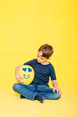 Full length of cute boy looking at yellow balloon with anthropomorphic face while sitting against colored background - p300m2199118 by Josep Rovirosa