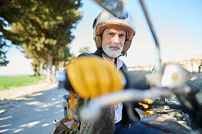 Mature man sitting on bike during road trip - p300m2275593 by Kiko Jimenez