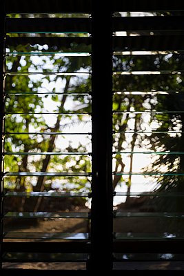 Blick auf den Strand durch ein Fenster mit Jalousie - p590m1564505 von Philippe Dureuil