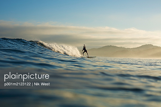 Silhouette paddle boarder riding ocean wave, Sayulita, Nayarit, Mexico - p301m2123122 by Nik West
