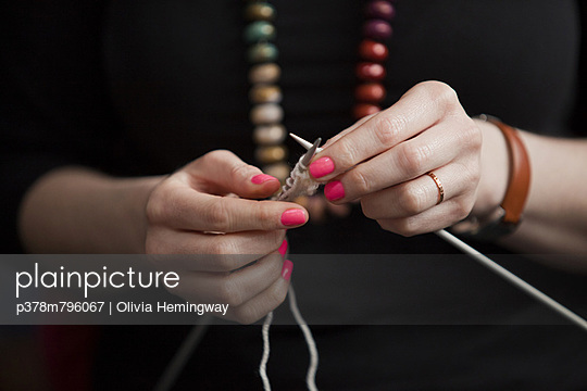 Hands knitting colourful nails - p378m796067 by Olivia Hemingway