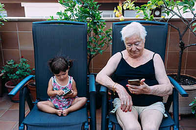 Grandmother and baby girl sitting side by side on the terrace using mobile phones - p300m2029089 by Gemma Ferrando