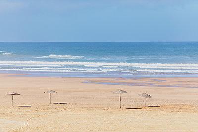 Morocco, empty beach, straw umbrellas - p300m2030037 von Michael Malorny