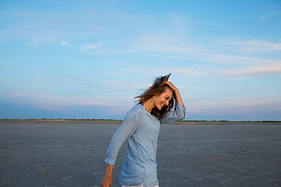 Young woman walks along the Wadden Sea - p341m1480719 by Mikesch