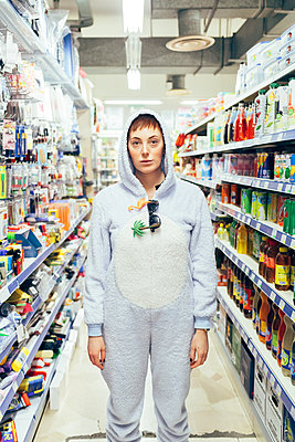 Portrait of woman wearing adult bodysuit in supermarket isle, looking at camera - p429m2019186 by Eugenio Marongiu