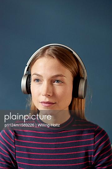 Junge Frau hört Musik über Kopfhörer - p1124m1589226 von Willing-Holtz