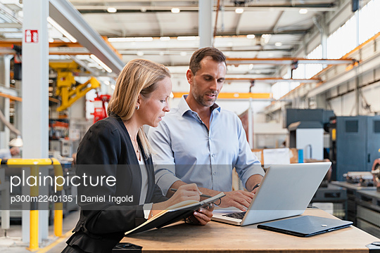 Female entrepreneur with book while male colleague working on laptop in factory - p300m2240135 von Daniel Ingold