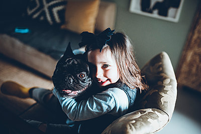 High angle portrait of happy girl embracing French Bulldog while sitting sofa at home - p1166m1474263 by Cavan Images