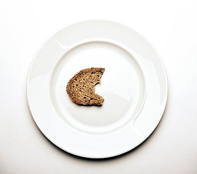 Scheibe Brot auf Teller - p1221m1025818 von Frank Lothar Lange