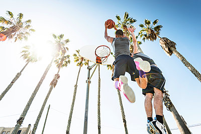 Two young men playing basketball on an outdoor court - p300m1140672 by Lighteffect