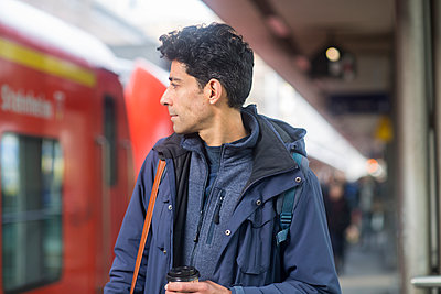 Man with backpack and coffee to go on platform - p300m1563079 by Sigrid Gombert