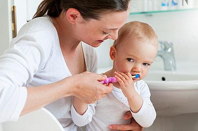 Mother brushing baby's teeth in bathroom - p300m1588147 von Daniel Ingold