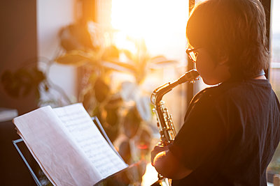 Boy exercising to play the saxophone at home in the evening - p300m2203155 by Valentina Barreto