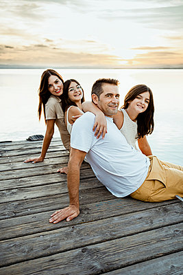 Happy family sitting at jetty against lake during sunset - p300m2241061 by Rafa Cortés