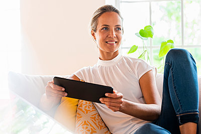 Smiling woman day dreaming while holding digital tablet on sofa - p300m2276406 by Steve Brookland