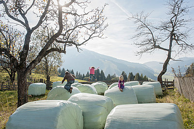 Three children playing on bales of straw - p300m949854f by Hans Huber