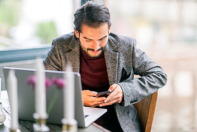 Young businessman using smartphone and laptop in cafe - p343m1585388 by Tamboly Photodesign