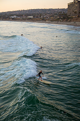 USA, California, San Diego, Surfer on water with beach and city in background - p352m1349556 by Andreas Ulvdell