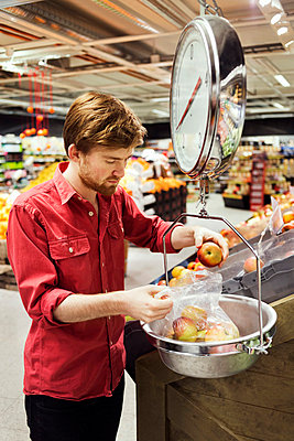 Young man weighing apples at supermarket - p426m1017992f by Maskot