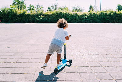 Toddler riding push scooter in park - p429m2078664 by Eugenio Marongiu