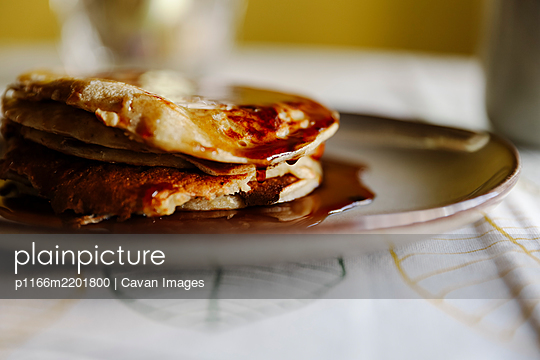Closeup yummy pancakes with sweet maple syrup placed on plate on table - p1166m2201800 by Cavan Images
