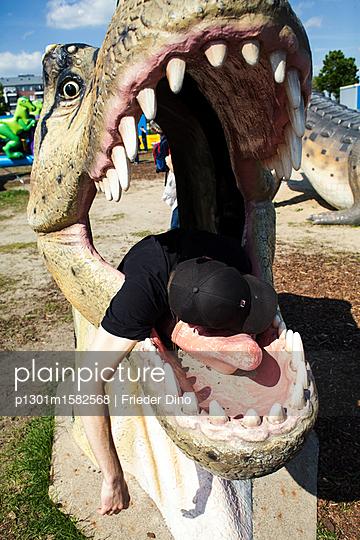 Junger Mann liegt in einem Dinosaurierkopf aus Plastik  - p1301m1582568 von Delia Baum