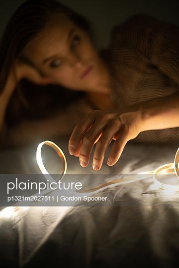 Junge Frau mit Lichterkette - p1321m2027511 von Gordon Spooner