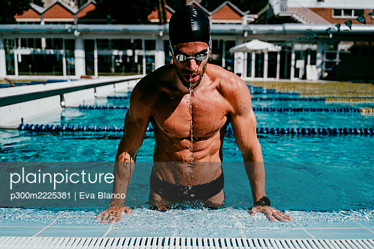 Muscular male swimmer getting out from swimming pool on sunny day - p300m2225381 by Eva Blanco