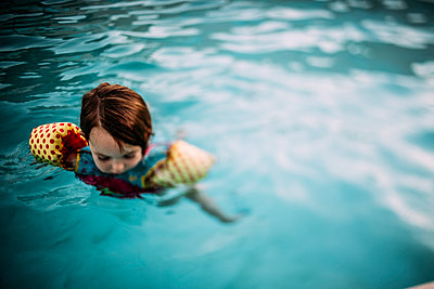 High angle view of cute girl wearing water wings while swimming in pool - p1166m2067653 by Cavan Images