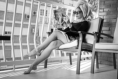 Glamour lady reading a magazine on balcony - p300m2132135 by DREAMSTOCK1982