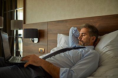 Businessman lying on bed in hotel room using laptop - p300m2171421 by Zeljko Dangubic
