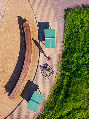 Russia, Tikhvin, Man with bicycle on boardwalk with table tennis tables, aerial view - p300m2202777 by Konstantin Trubavin