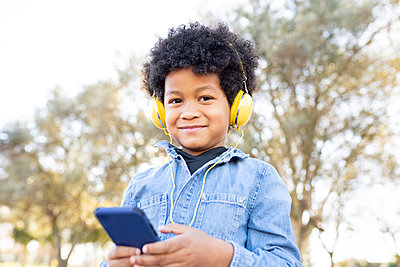 Smiling boy with headphones using mobile phone while standing at park - p300m2251892 by Jose Carlos Ichiro