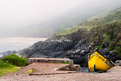 Yellow boat next to rocky cliffs on coastline of Cornwall, England - p352m2120165 by Mikael Ackelman