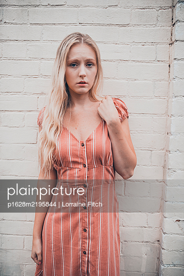 Young blonde woman in a pink dress - p1628m2195844 by Lorraine Fitch